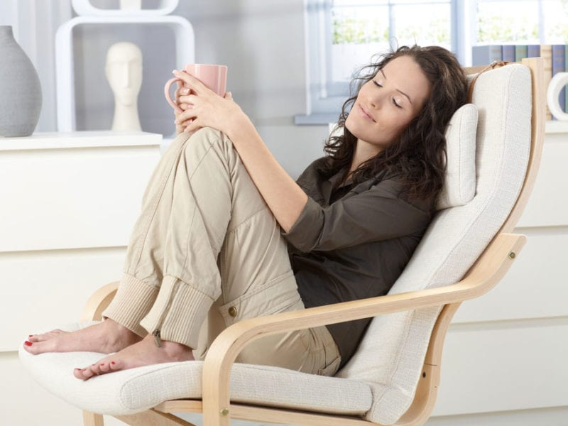 Woman sitting serenely in a chair and meditating