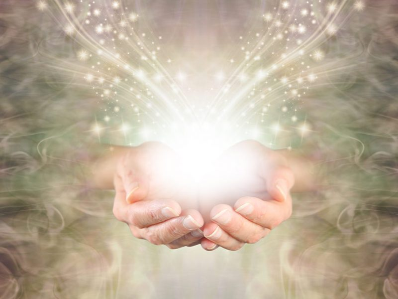 A pair of cupped hands emerging from green and gold swirling energy with shimmering sparkles of white light flowing outwards.