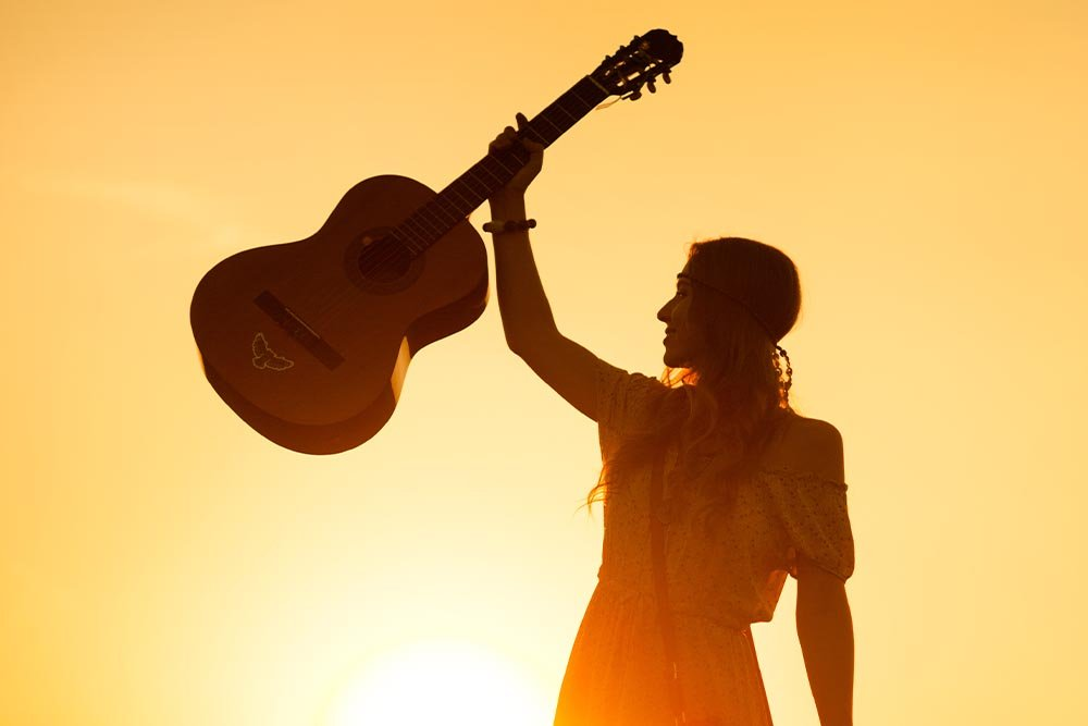 Silhouette of a woman wearing bohemian style clothing holding a guitar at sunset.