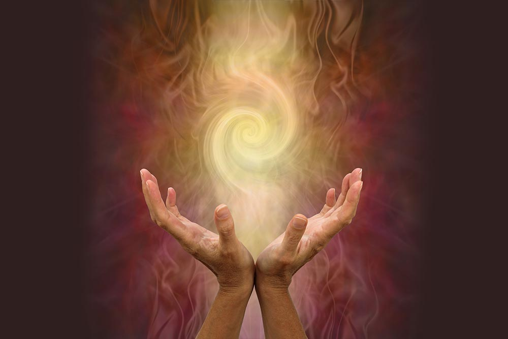 A pair of hands held open with a vortex of warm energy above on a reddish background.