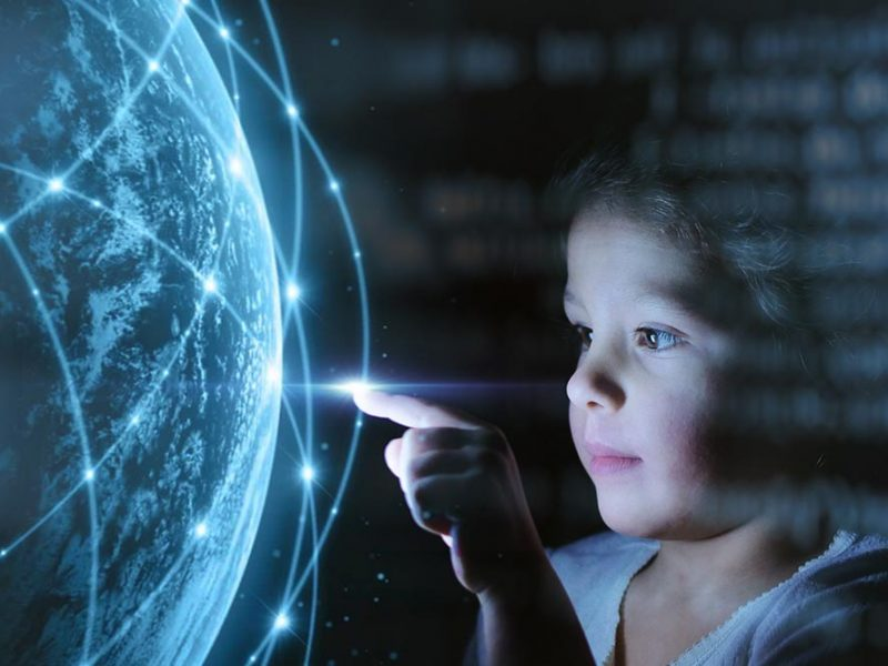 A little girl interacting with a digital wireframe globe.