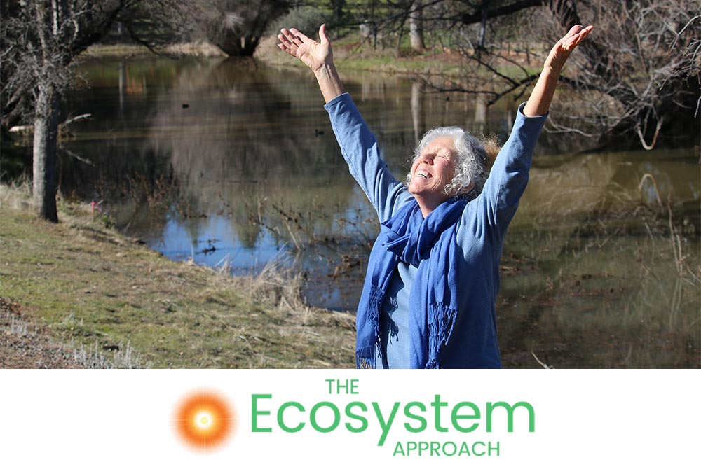 Patricia Rohn of The Ecosystem Approach with her arms happily outstretched towards the sky.