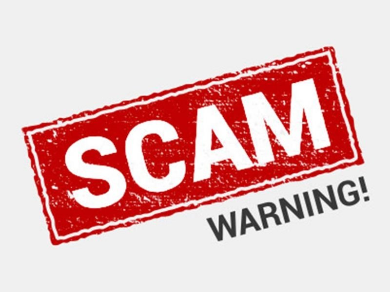 """""""Scam"""" written with a bright red stamp effect and """"warning!"""" typed below in black on a white background."""