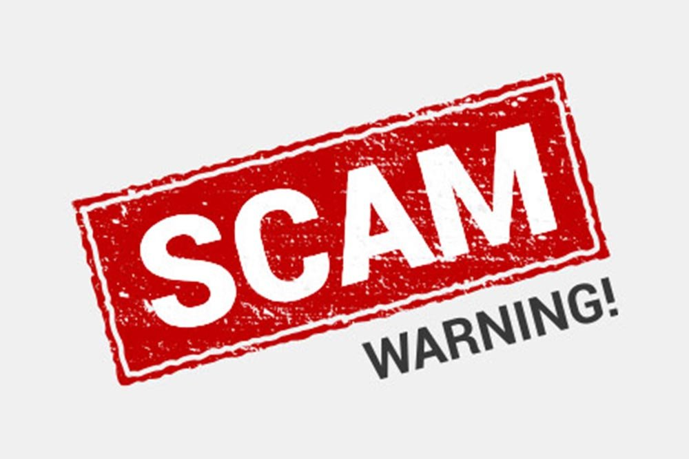 """Scam"" written with a bright red stamp effect and ""warning!"" typed below in black on a white background."