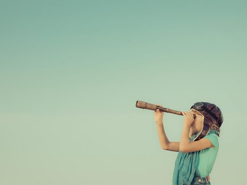 Little imaginative girl looking through a monocular scope on a blue background.