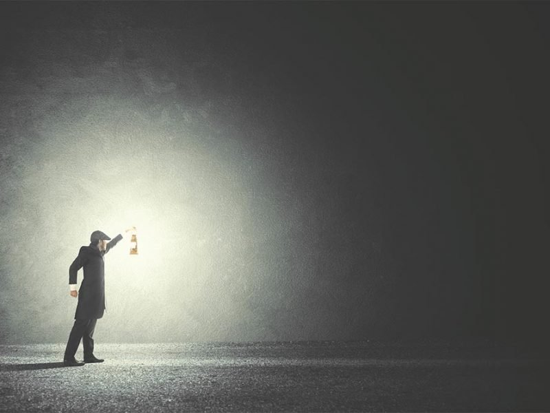 Image of a man in the dark illuminated by the gas lantern he is holding up.