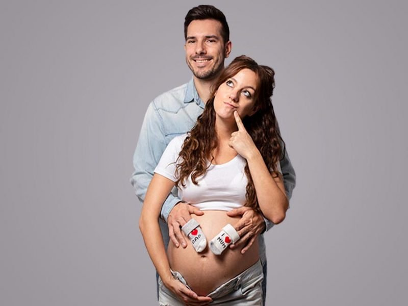 Thinking pregnant woman with a man craddling her bare belly.