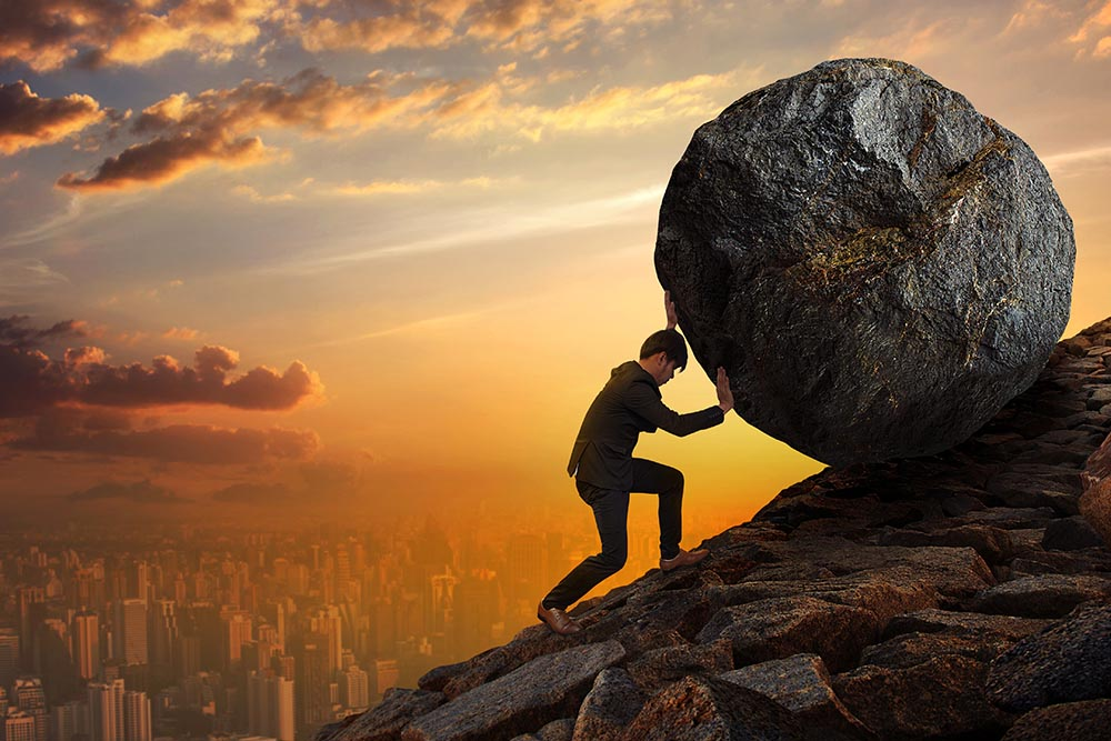 Man with a suit pushing a huge and heavy boulder up a hill at sunset.