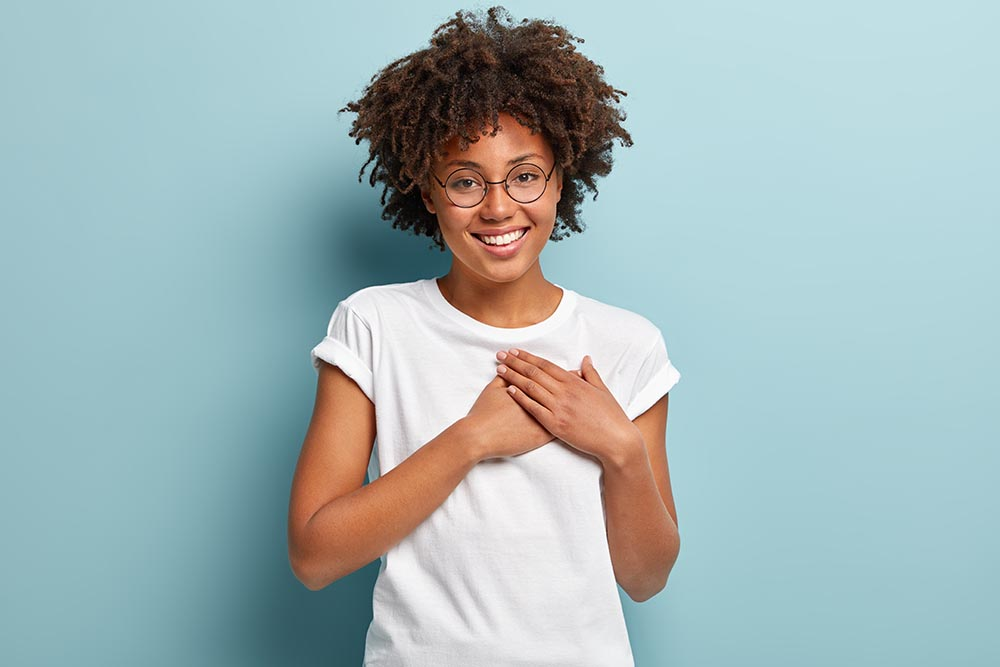 Happy woman wearing glasses and a white t-shirt holding her hands over her heart.