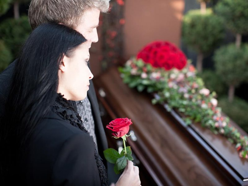 A couple at a funeral grieving the loss of a loved one.