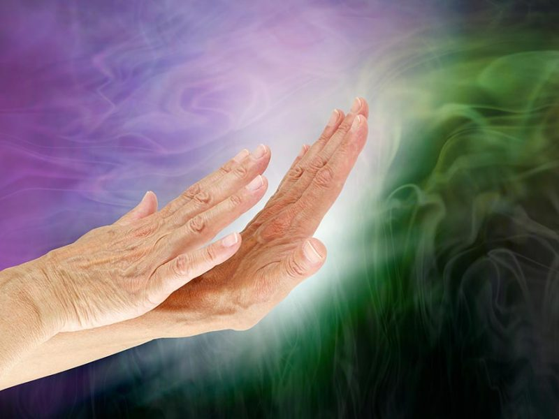 A pair of hands deflecting negative purple and green energy waves.
