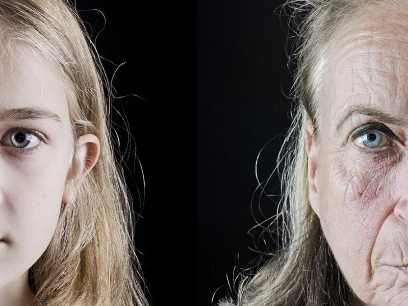 A young girl and old woman side-by-side on a dark background.