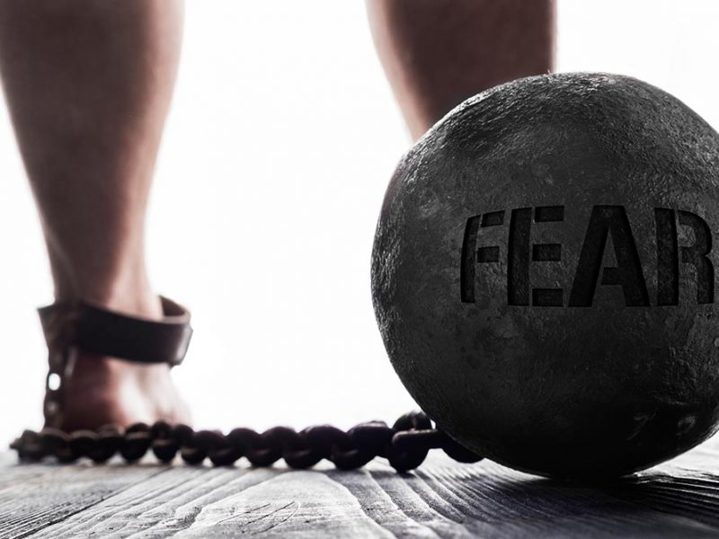 A person with a ball and chain connected to their ankle. The ball reads 'FEAR'.