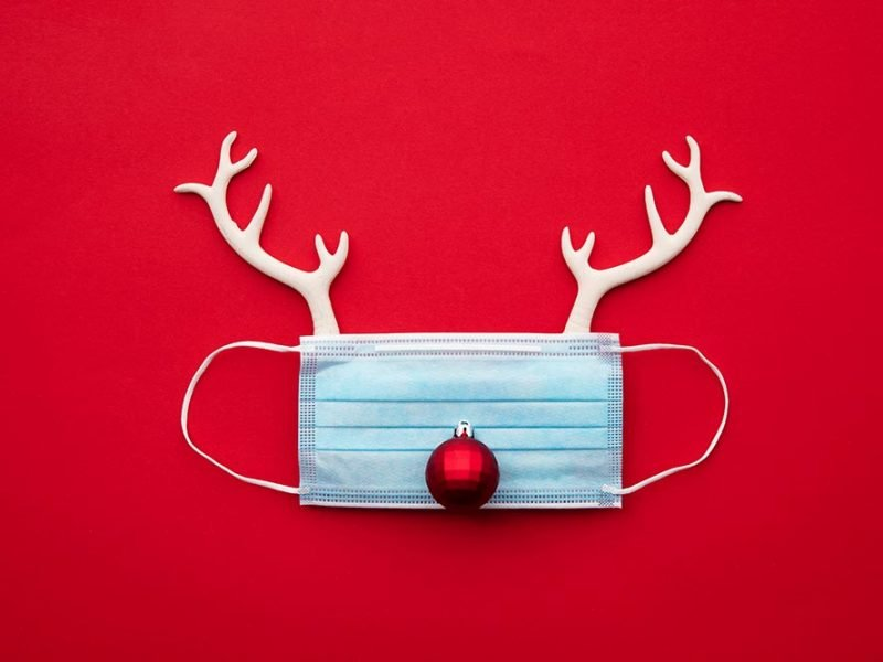 Disposable face mask on a red background with a red ornament nose and two antlers above.