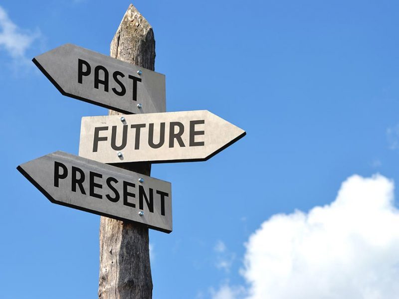 Three direction signs pointing to the past, future, and present.