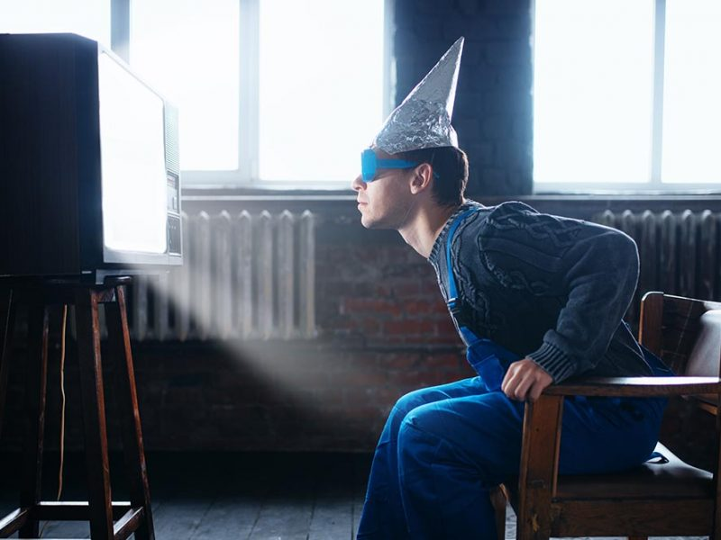 Adult man wearing, overalls, a tin foil hat, and large glasses staring closely at a bright tv.