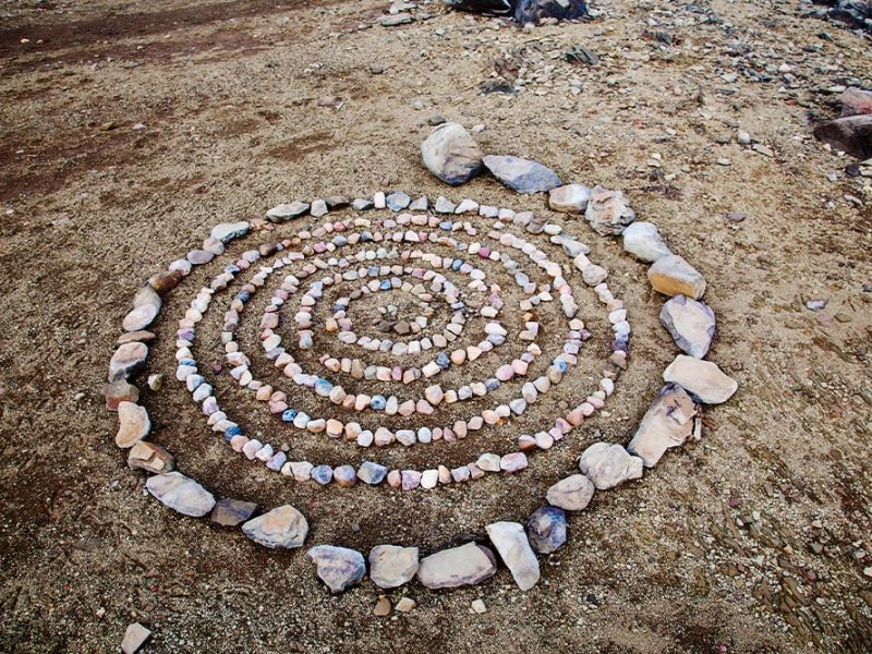 A large spiral composed of rocks in the sand.