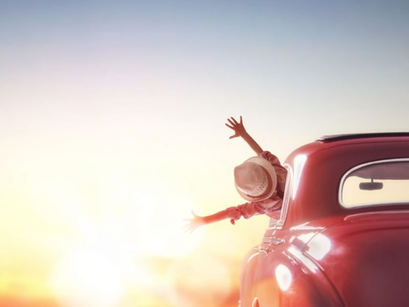 A woman with a hat riding off into the sunset in a vintage car with her hands extended out of the window happily