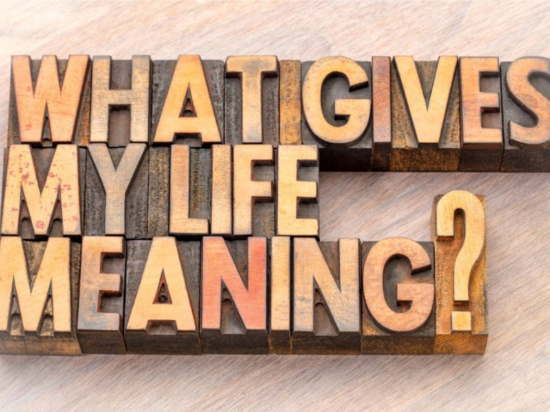 """Wooden block letters on a wood background spelling out """"what gives my life meaning?"""""""