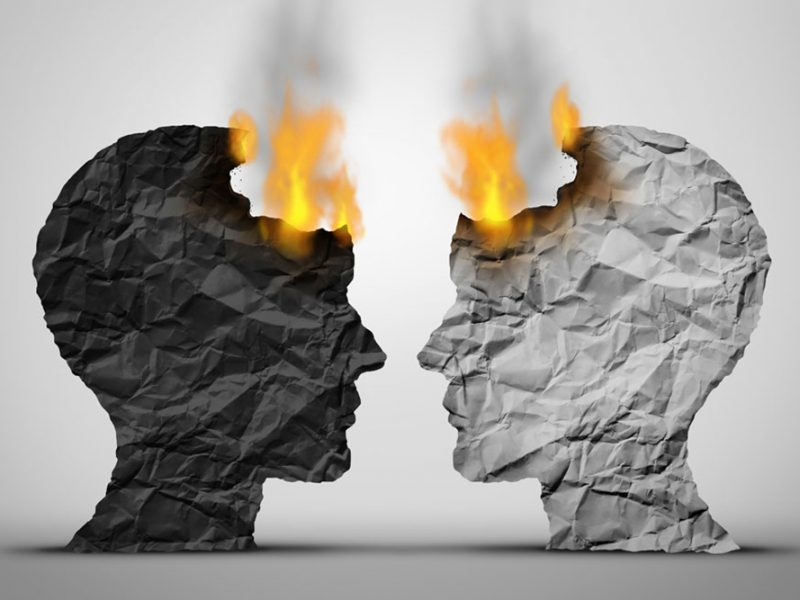 Crumpled paper cut outs on fire at the frontal lobe of a black and white human head facing one another