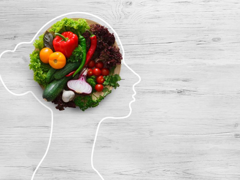 Silhouette drawing of a woman from the side with a round plate of a variety of vegetables where her brain should be
