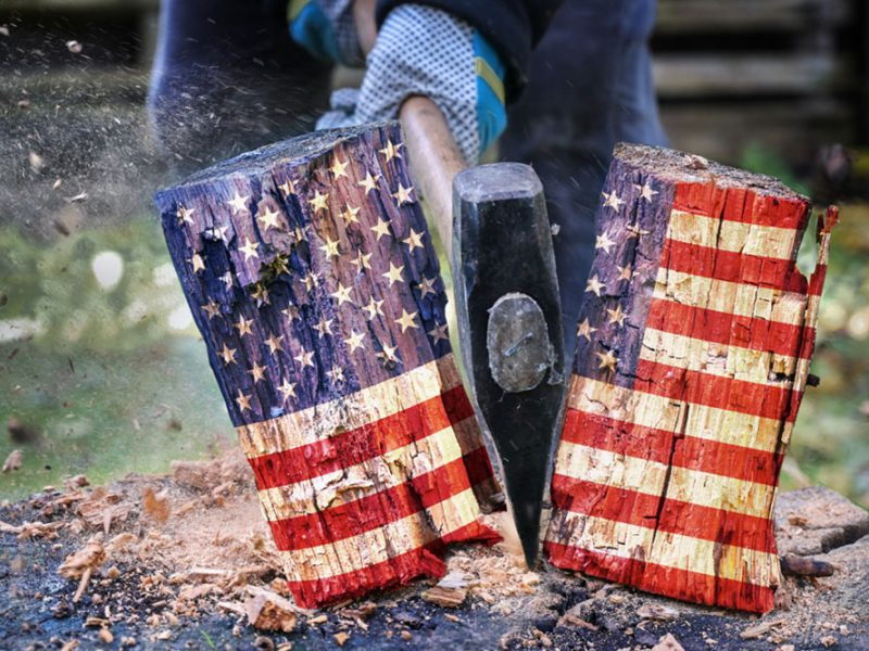 Wooden block with the American flag painted on it and person with an axe splitting the block in half