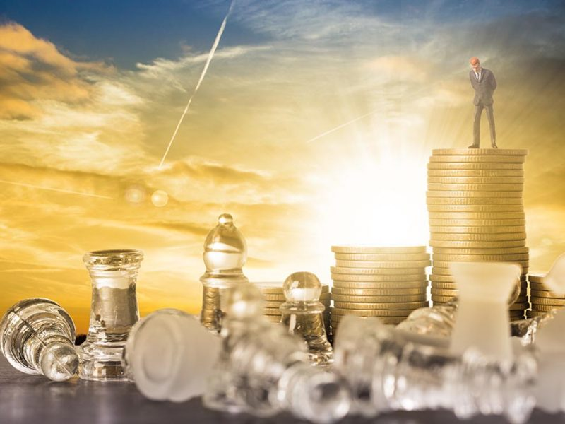 Vector image of a man in a suit standing on a large pile of gold coins at sunrise with large class chess pieces surrounding him and toppled over