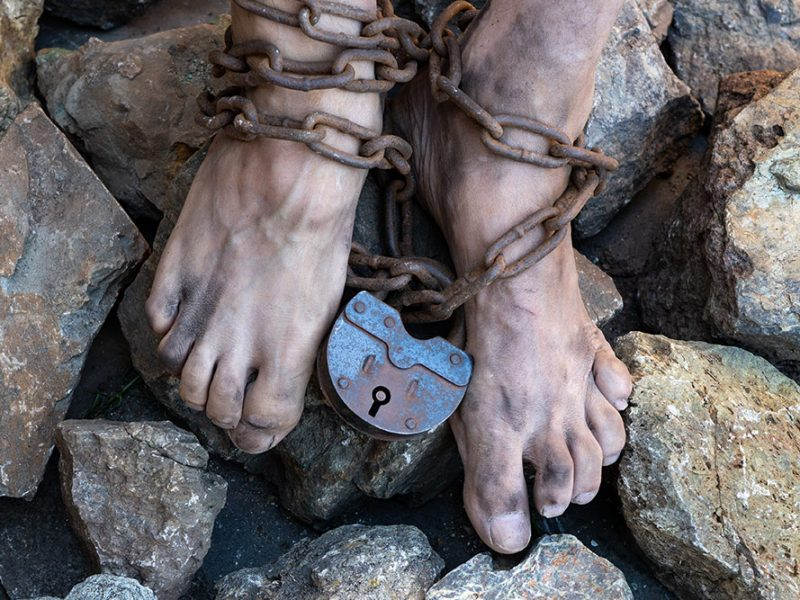 Bare and dirty feet standing on jagged rocks with rusted chains and a large padlock around their ankles