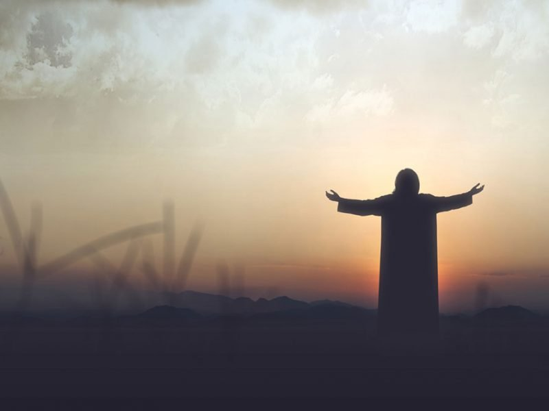 Rear silhouette of Jesus with his arms outstretched in the sunset