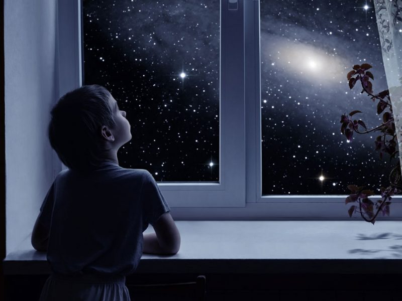 Child looking out of a window at night at the starry sky