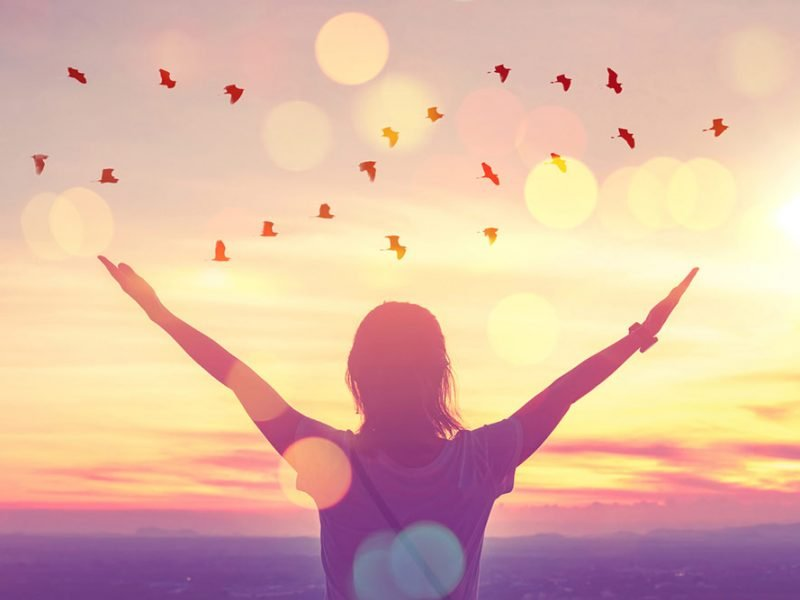 Woman facing sunset at golden hour with her arms outstretched in a V shape and birds flying overhead