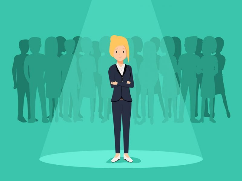 Vector image of a smiling woman wearing a suit with her arms crossed and standing in a spotlight with a silhouette of a crowd behind her