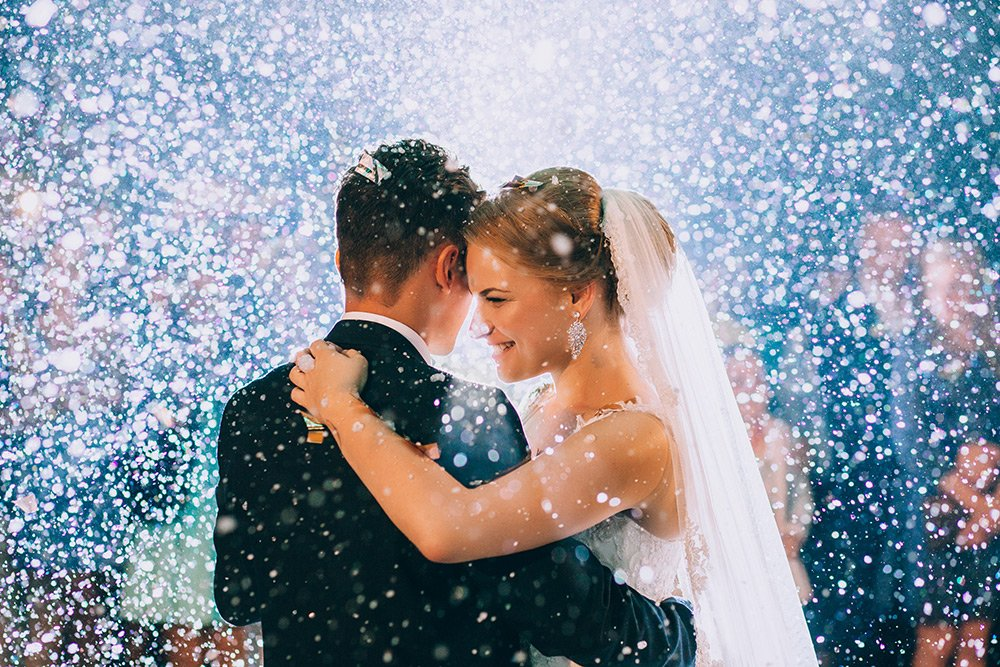 A young couple on their wedding day dancing with blurred faces in the background and flecks of white light like snow all around them