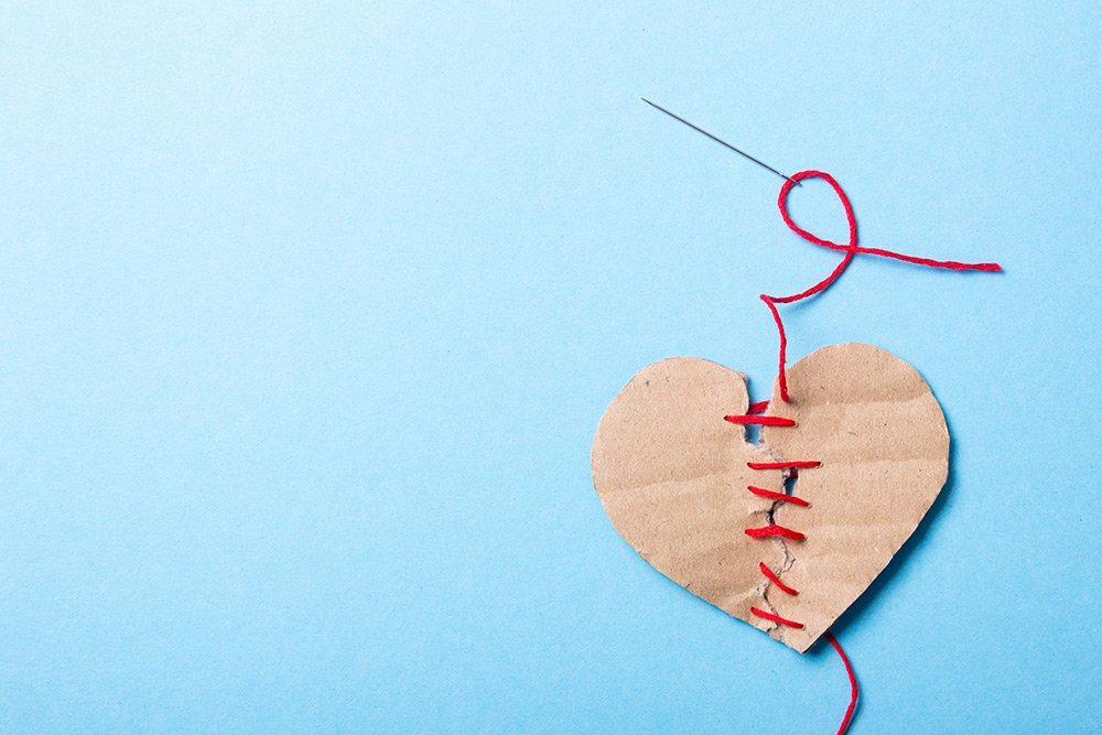 Image of a cardboard heart torn in half and being stitched back together with red ribbon
