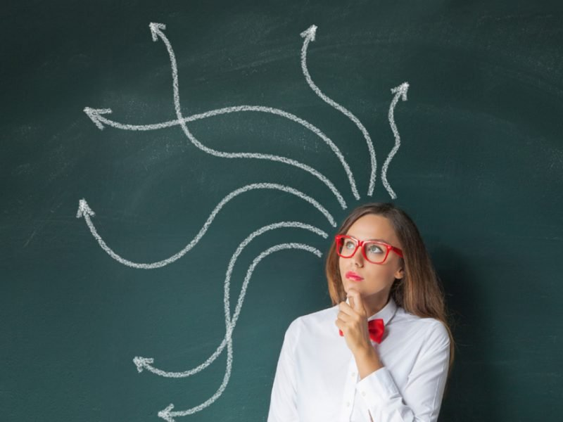 Woman in red glasses and a white button up with a red bowtie pensively standing in front of a chalkboard with chalk arrows drawn behind her from her head