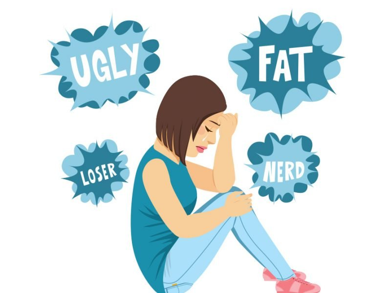 Vector image of a young woman sitting down crying with the words ugly, fat, loser, and nerd floating around her