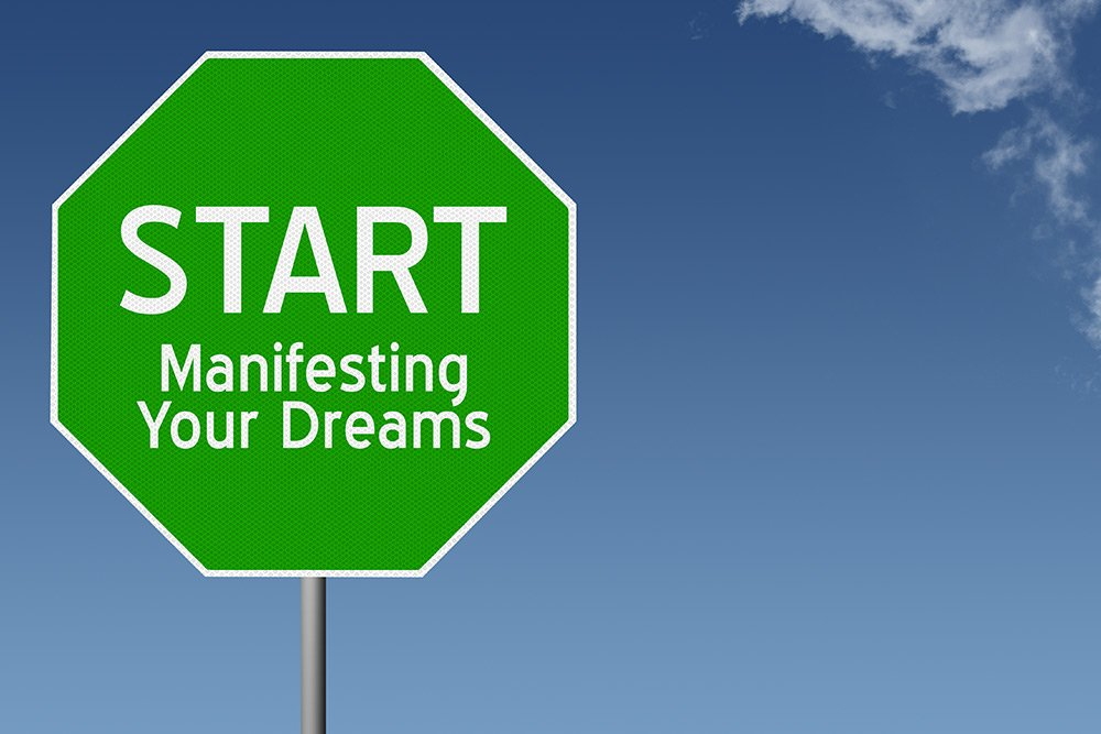Image of a green stop sign that says start manifesting your dreams