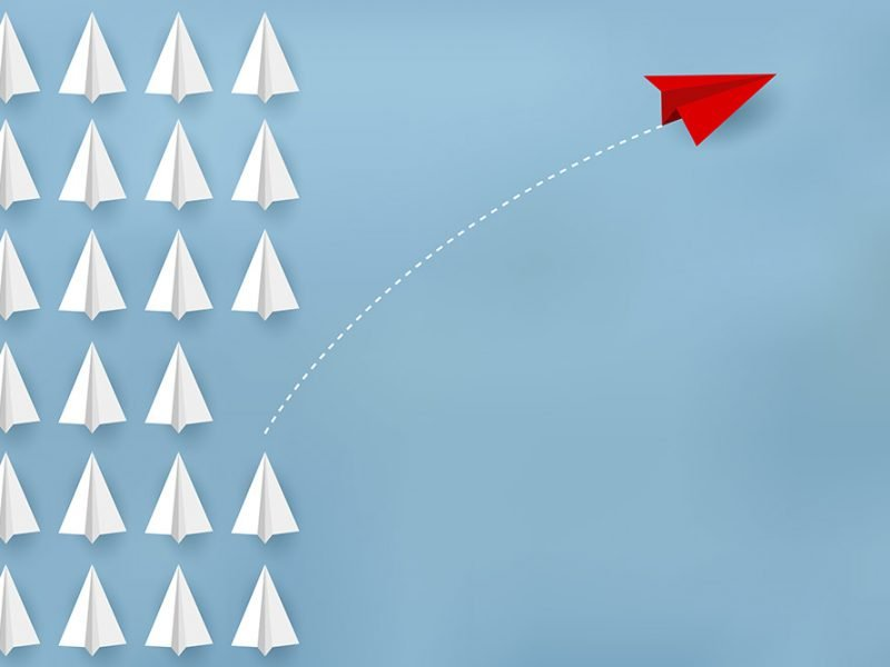 Image of several white paper planes sitting in neat 6x4 rows with a red paper plane taking a hard right turn from one of the lines where there is a missing spot