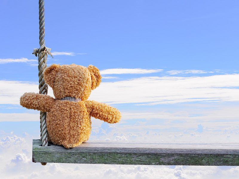 Rear view of a teddy bear sitting on a wooden swing sitting above the clouds on a beautiful day