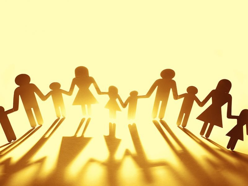 Cardboard cutouts of stick figures of a family of four joining hands across a yellow background with a light behind them to cast shadows