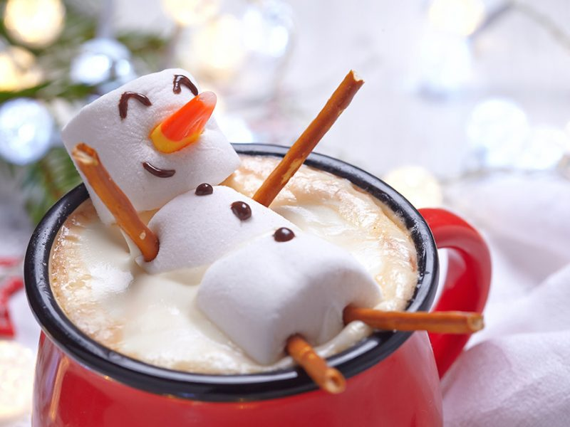 Closeup image of a mug of hot cocoa with a snowman made of marshmallows and candy on top of the mug