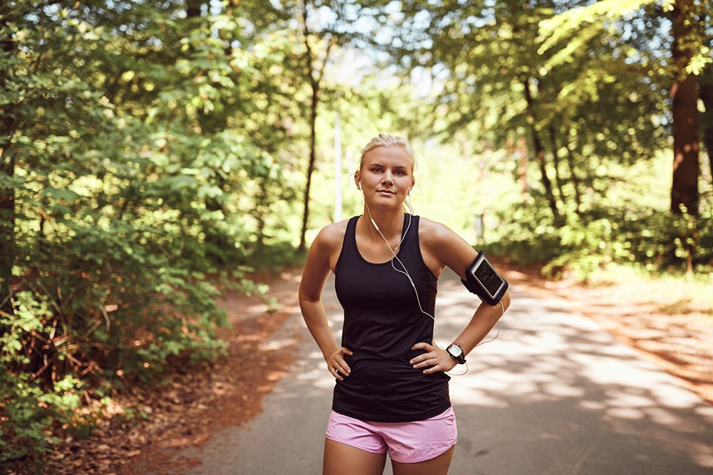Young woman in workout attire standing on a running trail in a park with headphones in and her arms crossed and looking forward