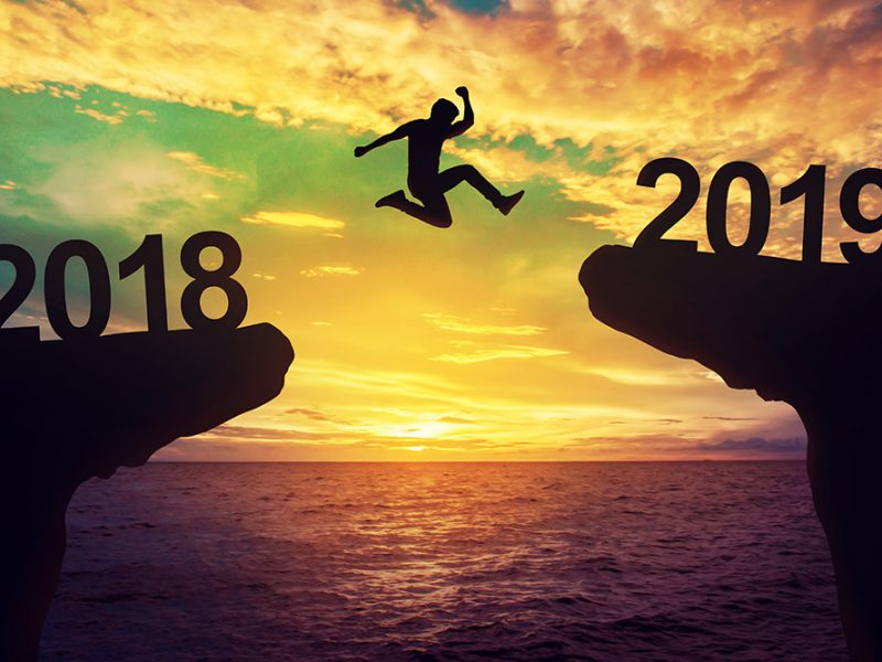 Silhouette of a man jumping from one cliff with 2018 written on it to another cliff with 2019 written on it over an ocean at sunset