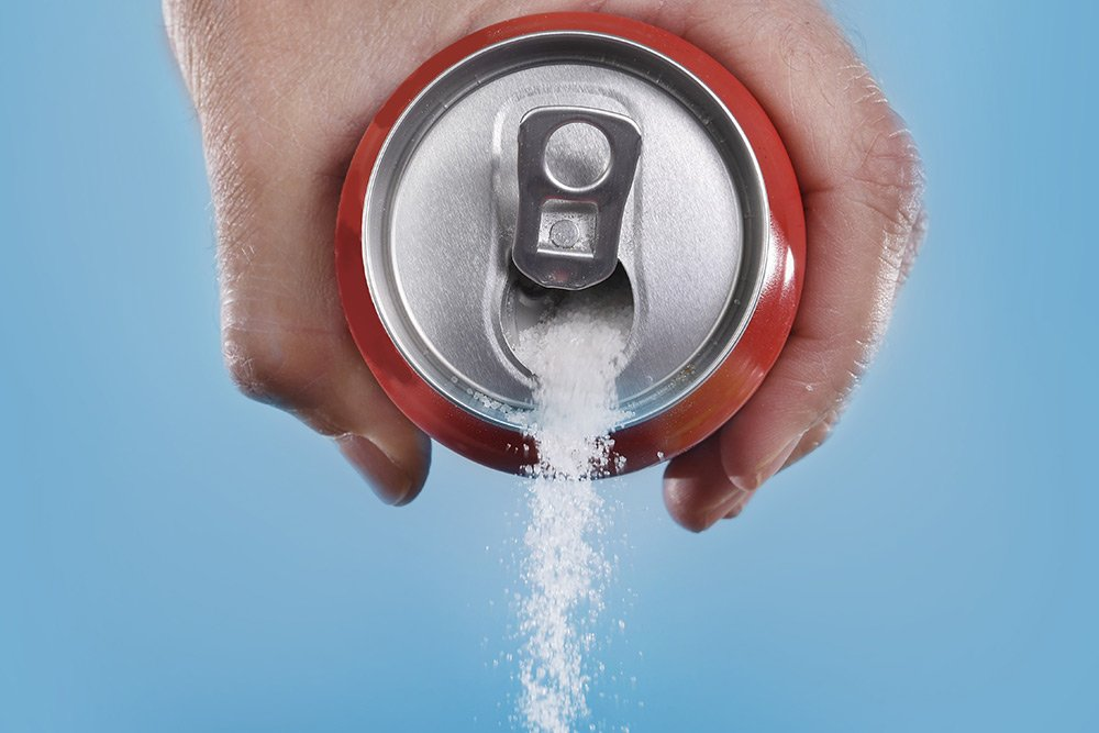 A man's hand grabbing a can of soda from the side and pouring out sugar instead of soda from the can
