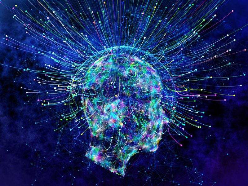 Image of a person's brain neural pathways leading out of the brain lit up in varying colors on a dark and inky sky background