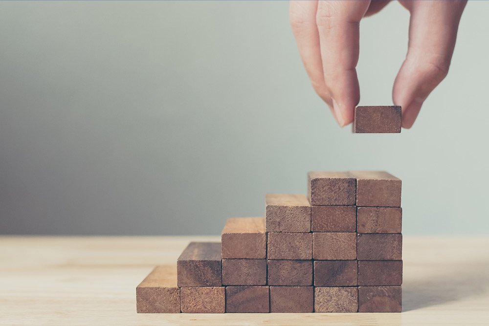 A closeup of wooden blocks being stacked in the shape of stairs by a large hand about to place the final step at the top