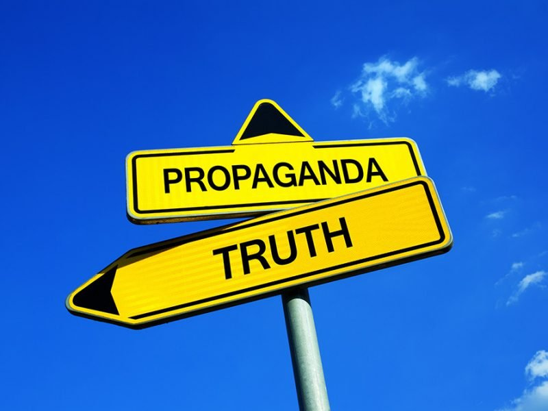 Yellow arrow signs saying truth pointing to the left and propaganda pointing upwards towards a bright blue sky