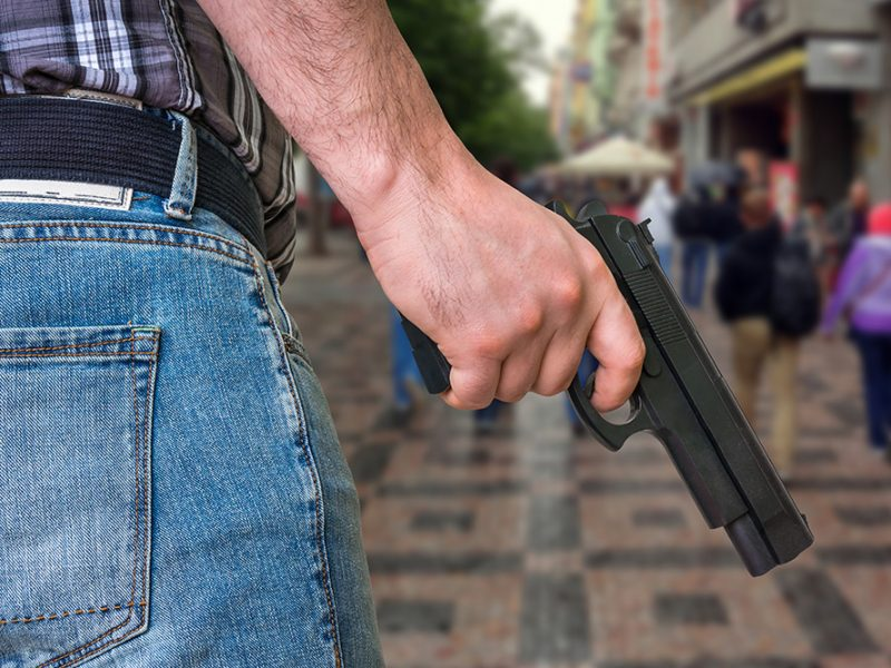 Closeup of a man's hand holding a gun in a public area with people in the background