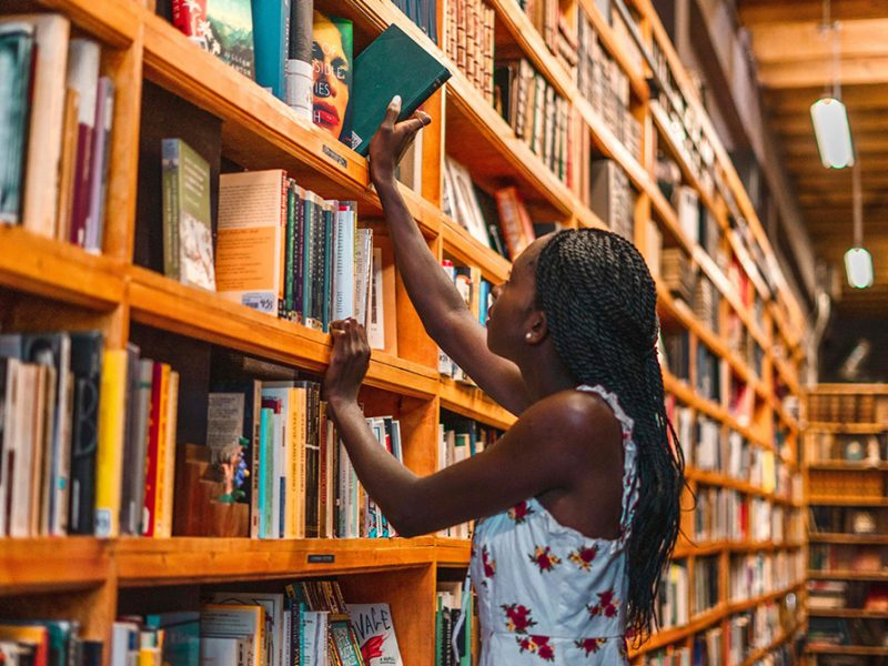 A young woman in a library reaching above her head to grab a book off of a higher shelf
