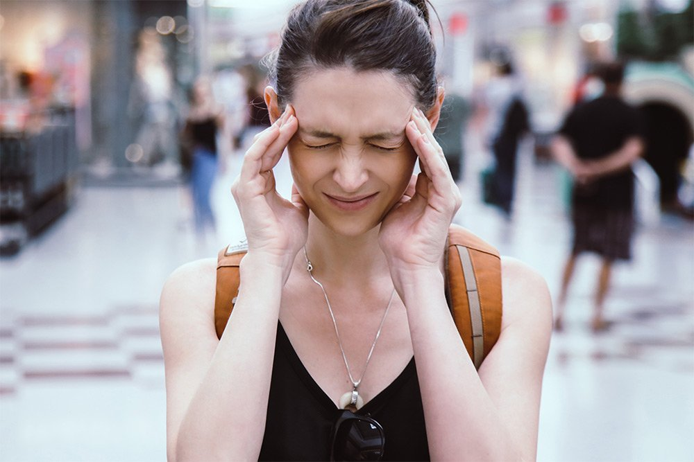 Young woman having a migraine headache in public with her hands to her head and eyes squinted shut in pain